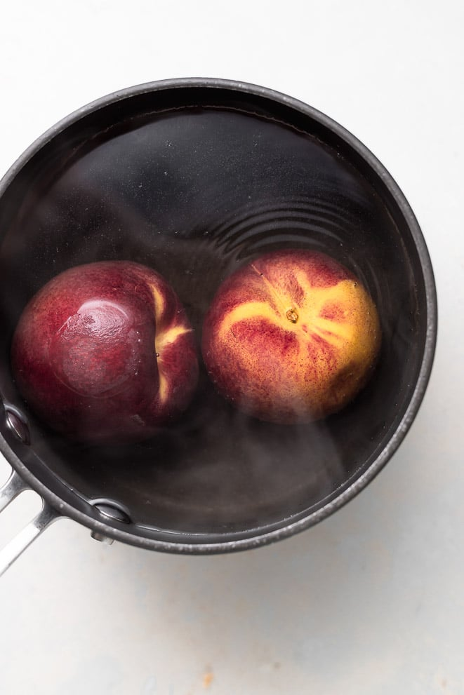 two peaches sitting in a black pot of hot boiling water