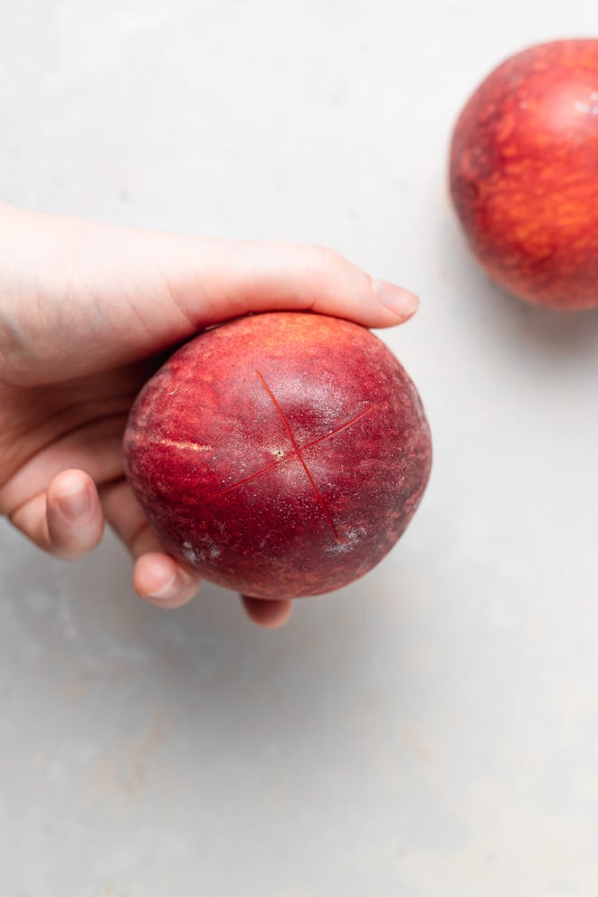 a hand holding a peach that has been scored with an X on the bottom