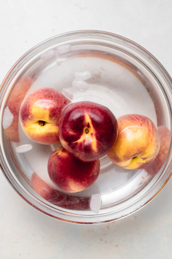 four peaches sitting in a large bowl of ice water