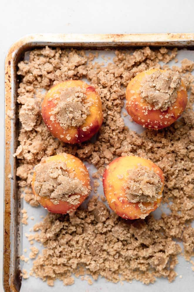 a baking sheet with the pie crumble around four peaches that are also topped with the pie crumb