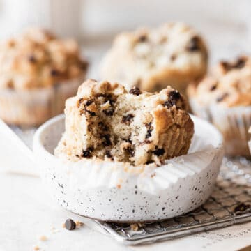 a muffin with a bite taken out of it sitting in a white ceramic dish