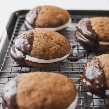 whoopie pies on a wire rack dipped half in chocolate