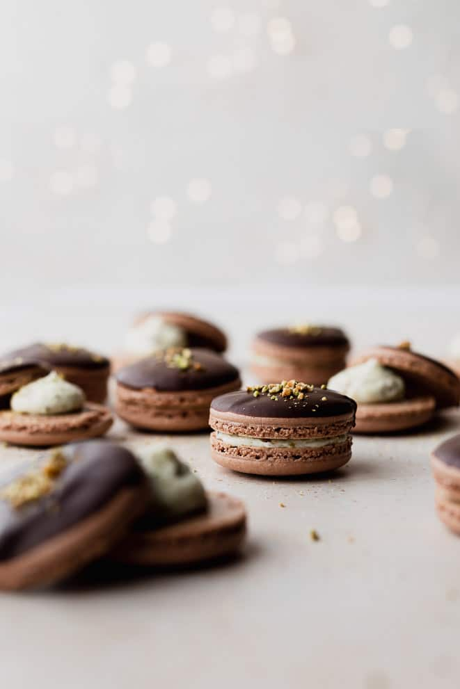 up close shot of chocolate macaron filled with pistachio butter cream and dipped in chocolate