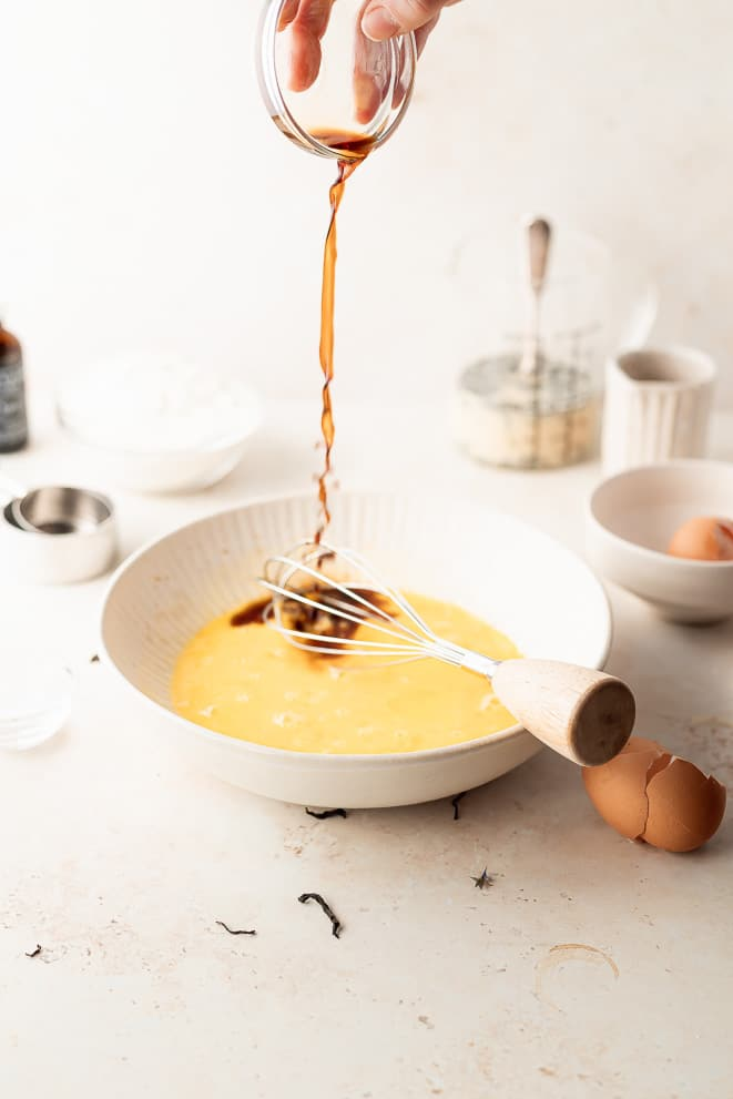 pouring the vanilla into the bowl of wet ingredients