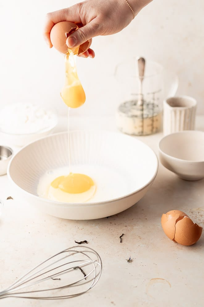an egg dropping into the bowl with the milk