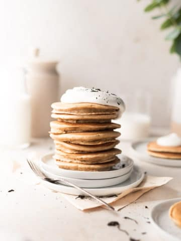pancakes stacked on top of each other and topped with whipped cream