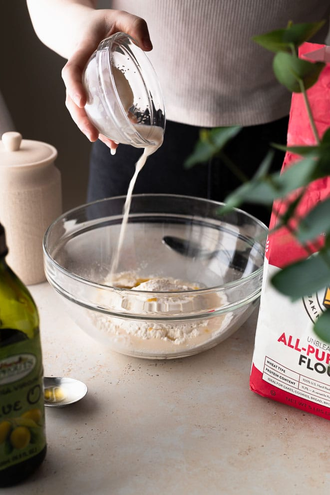 adding the yeast and water to the flour