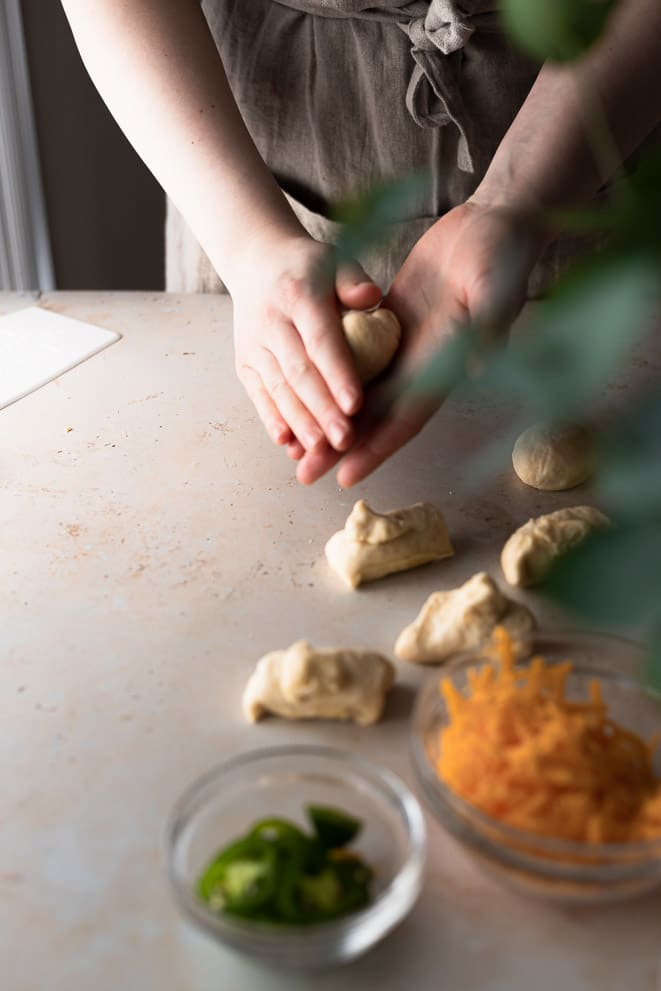 rolling each dough portion into a ball