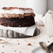 the cake topped with whipped cream and dusted with cocoa powder sitting on an upside down round pan