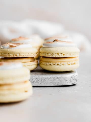 macarons on a silver tray topped with toasted meringue