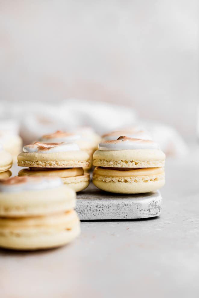 banana crema pie macarons lined up on a baking tray