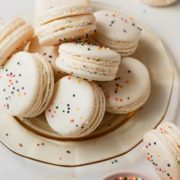 macarons on a plate surrounded by sprinkles