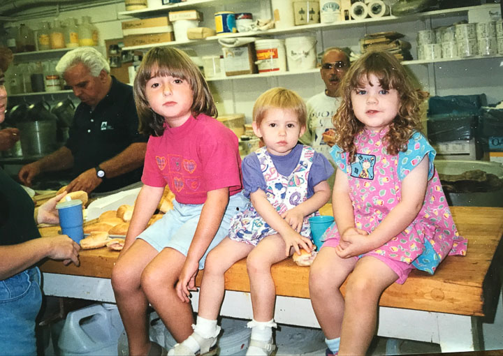 three young girls sitting on a bakery counter