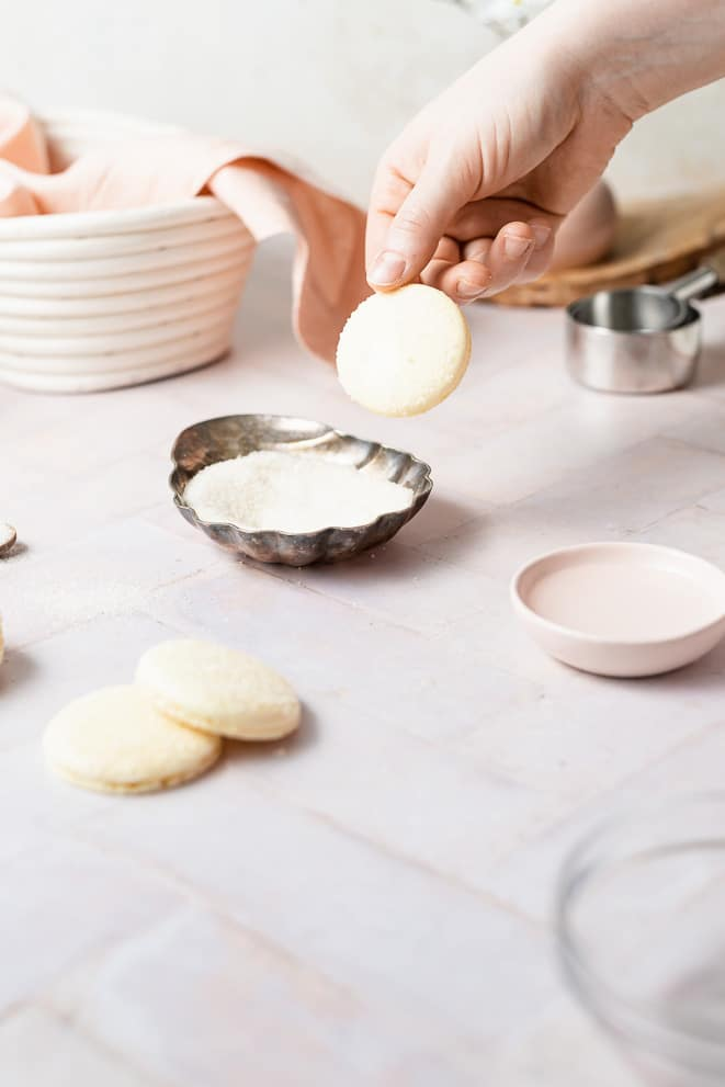 dipping the shells into a bowl of sugar