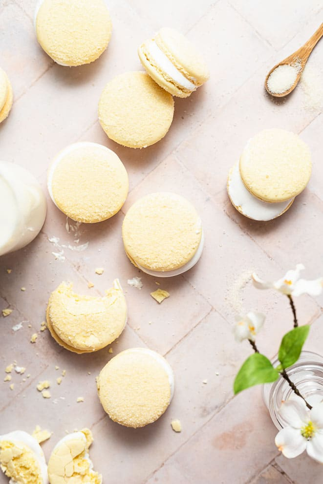 marshmallow macarons on a pink background with sugar sprinkled around them