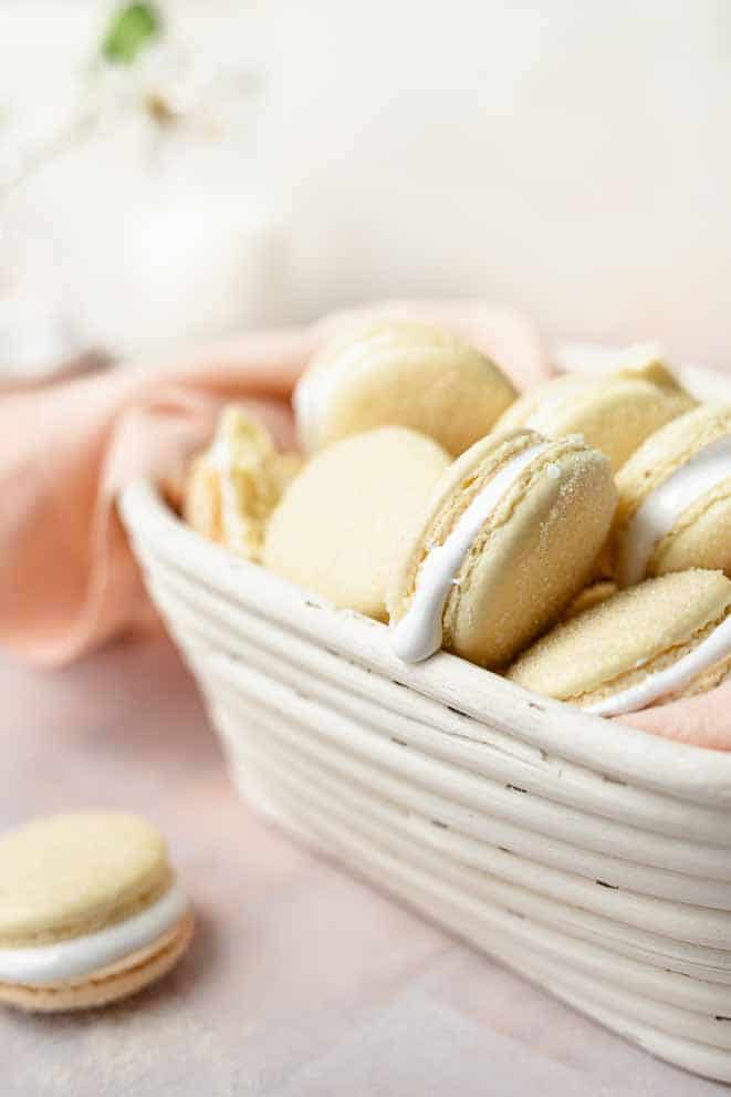 basket full of marshmallow macarons and a peach colored linen