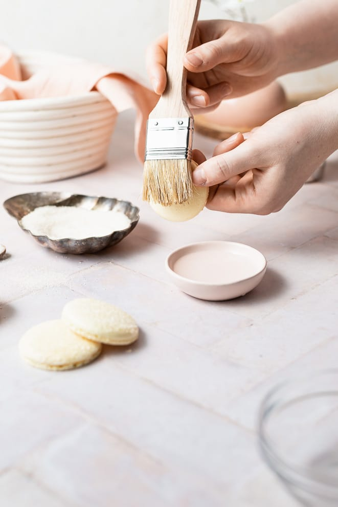 brushing water on top of the macaron shells