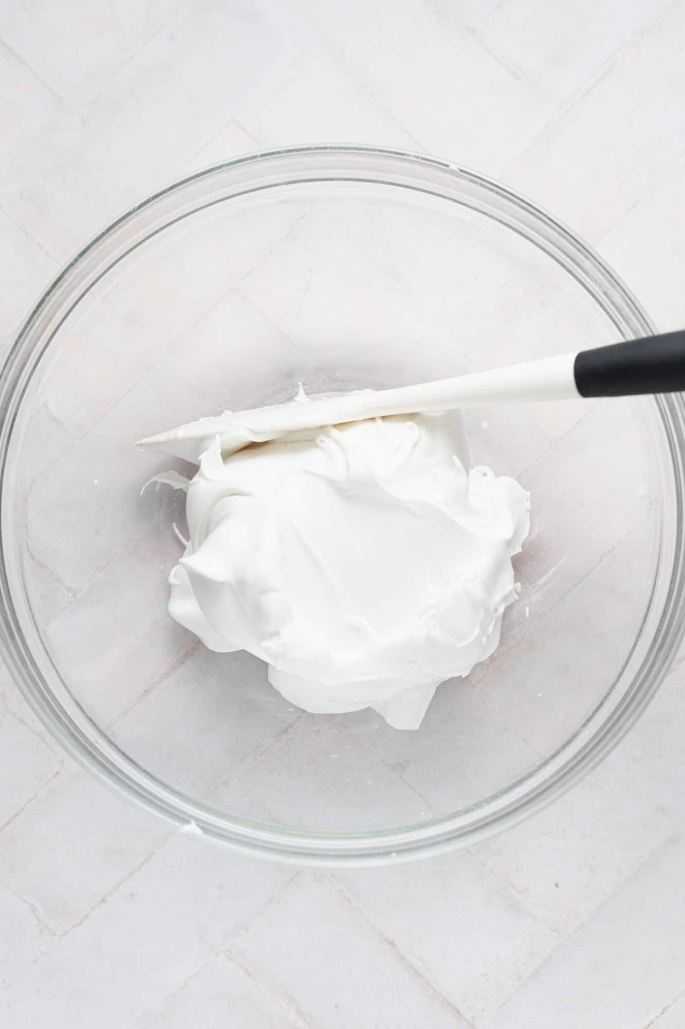 stiff egg whites in a bowl with a spatula