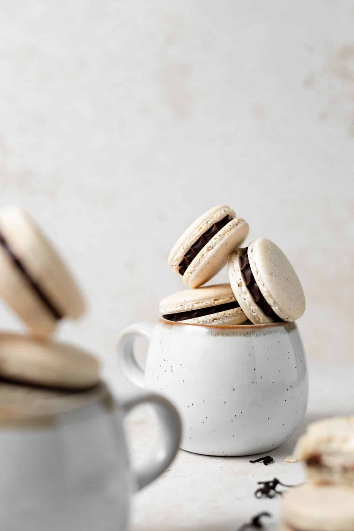 a cup of earl grey macarons stacked.