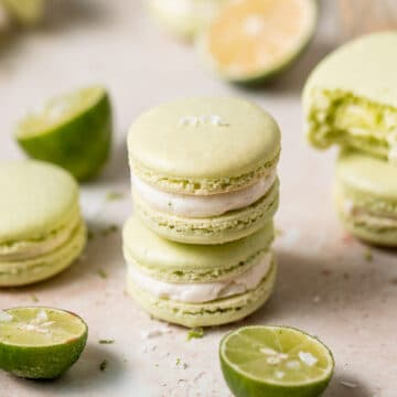 two macarons stacked on top of each other with fresh limes beside it