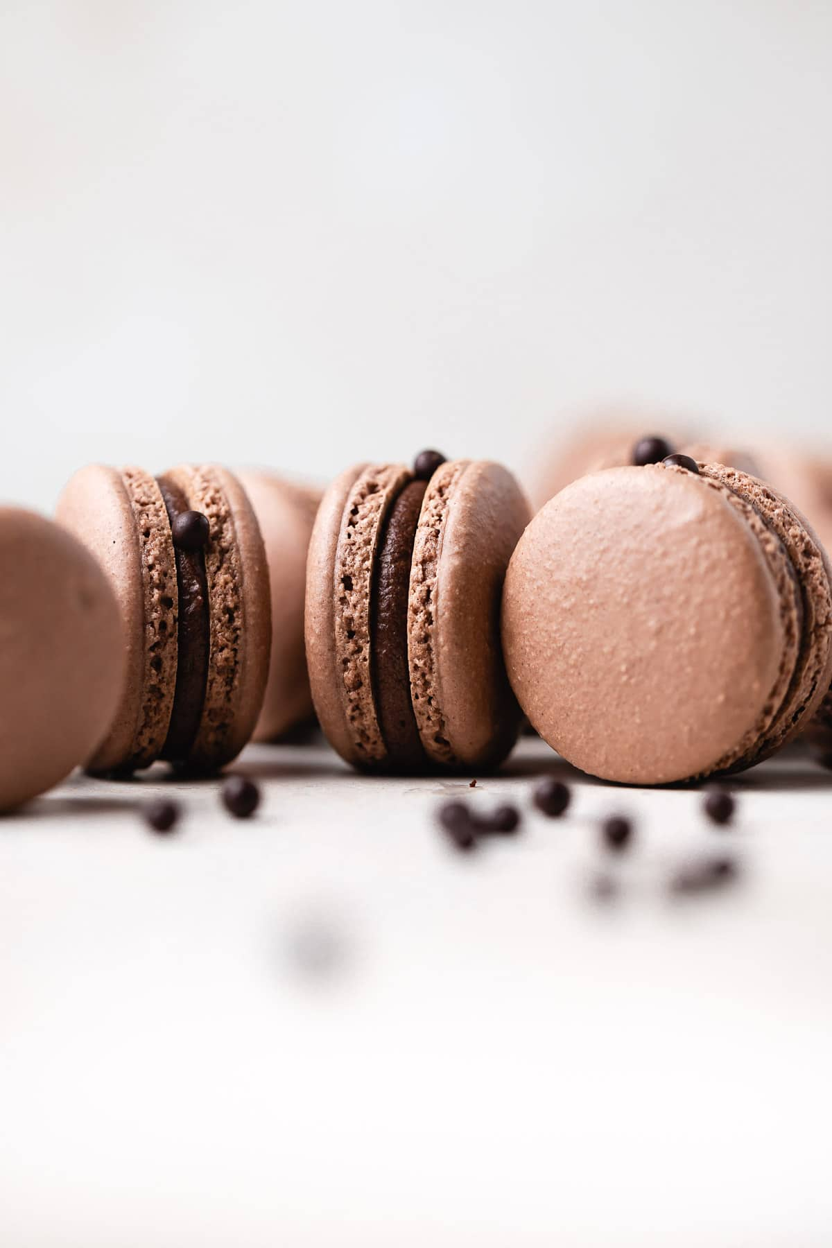 a few macarons sitting on their sides with milk balls around it