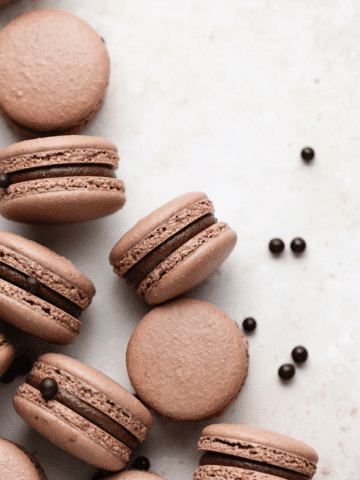 overhead shot of macarons arranged randomly on a surface surrounded by malt balls