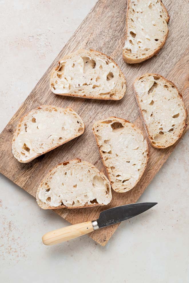 slices of sourdough bread on a cutting board smeared with butter