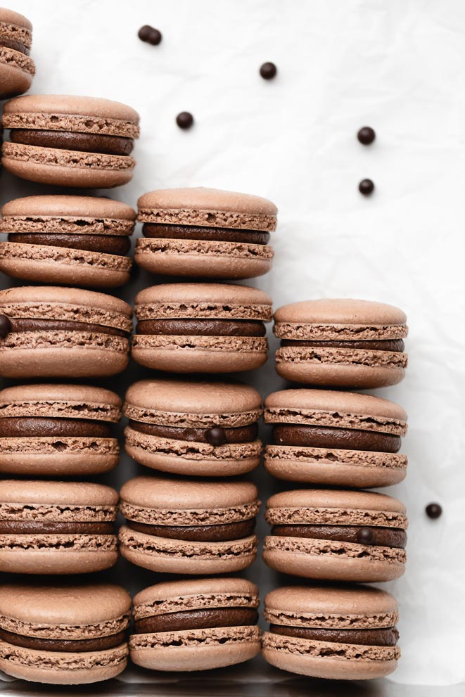 three stacks of malted dark chocolate macarons on a white surface with mini malt balls around them