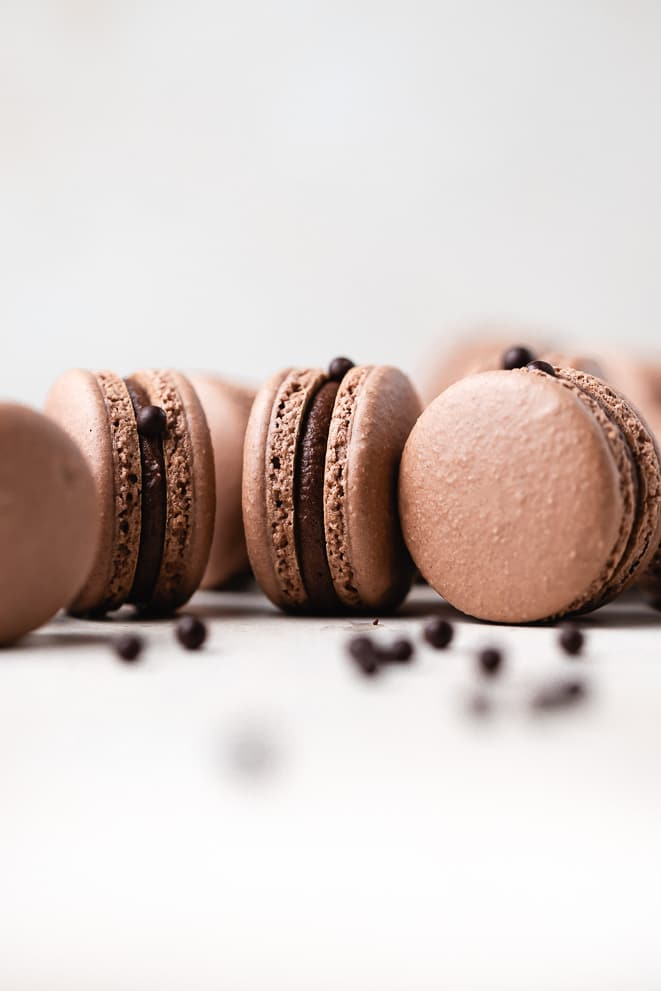 malted dark chocolate macarons on a white surface sitting on their sides surrounded by mini malt balls