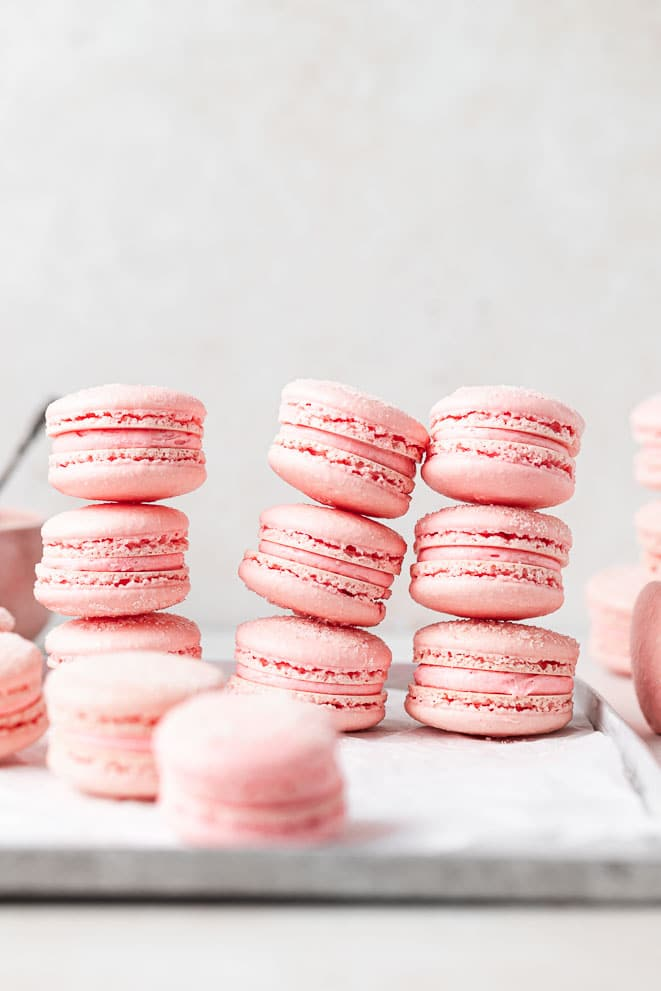 three stacks of three sour watermelon macarons sitting on a metal tray