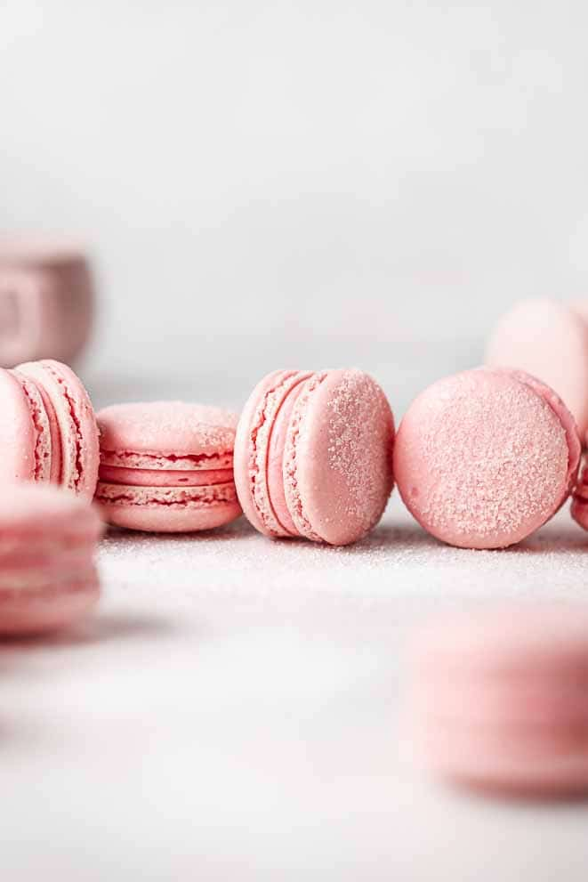 sour watermelon macarons on their side with sugar sprinkled around them