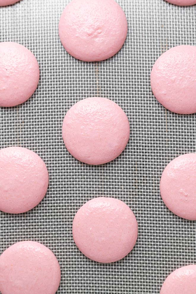 pink sour watermelon macaron shells piped in circles on a silicone baking mat
