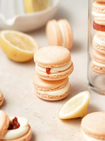 two stacked strawberry lemon macarons surrounded by fresh lemons