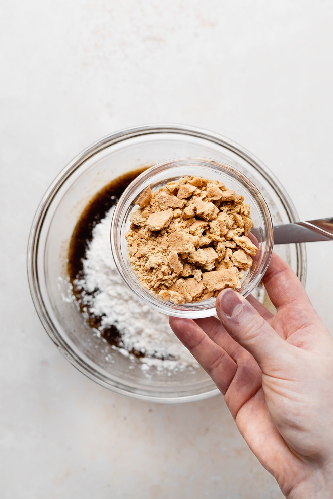 bowl of graham cracker crumbs being added to the bowl of cookie dough