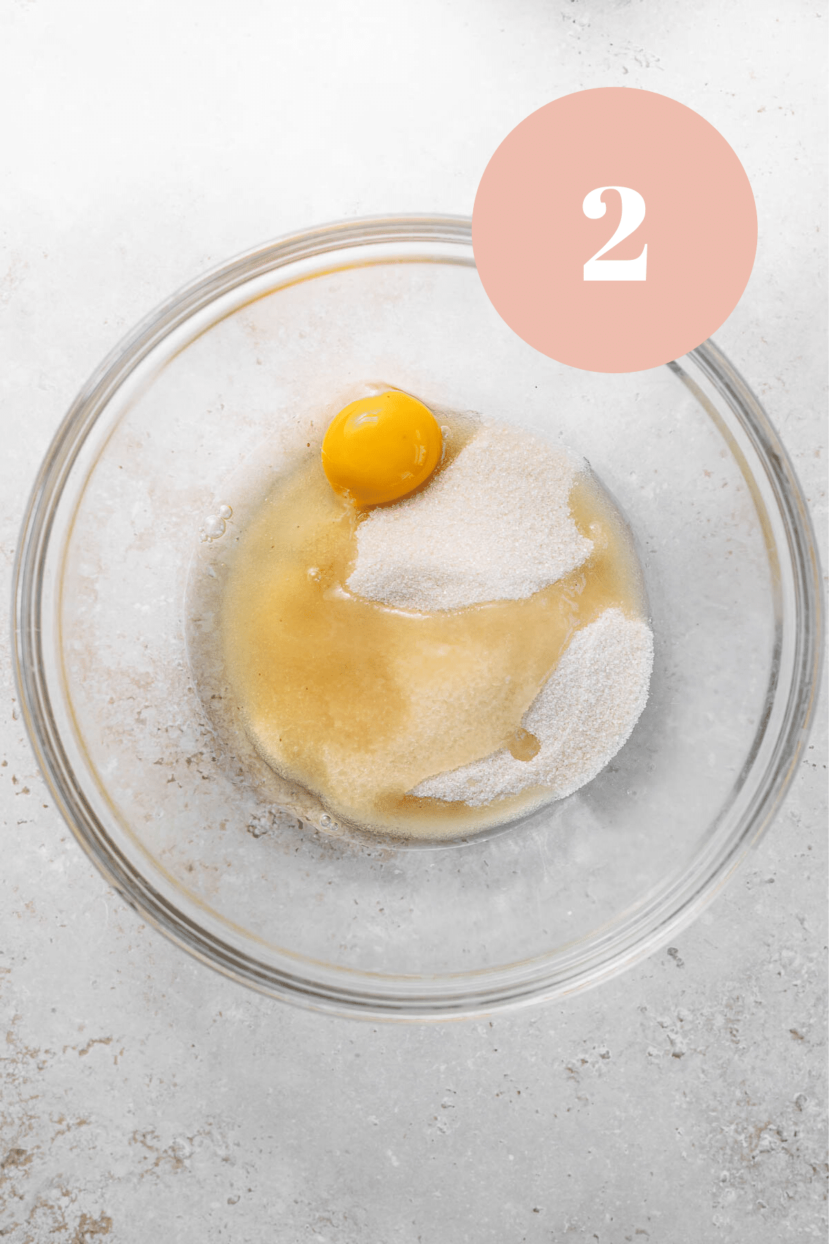 a bowl of sugar and eggs before mixing