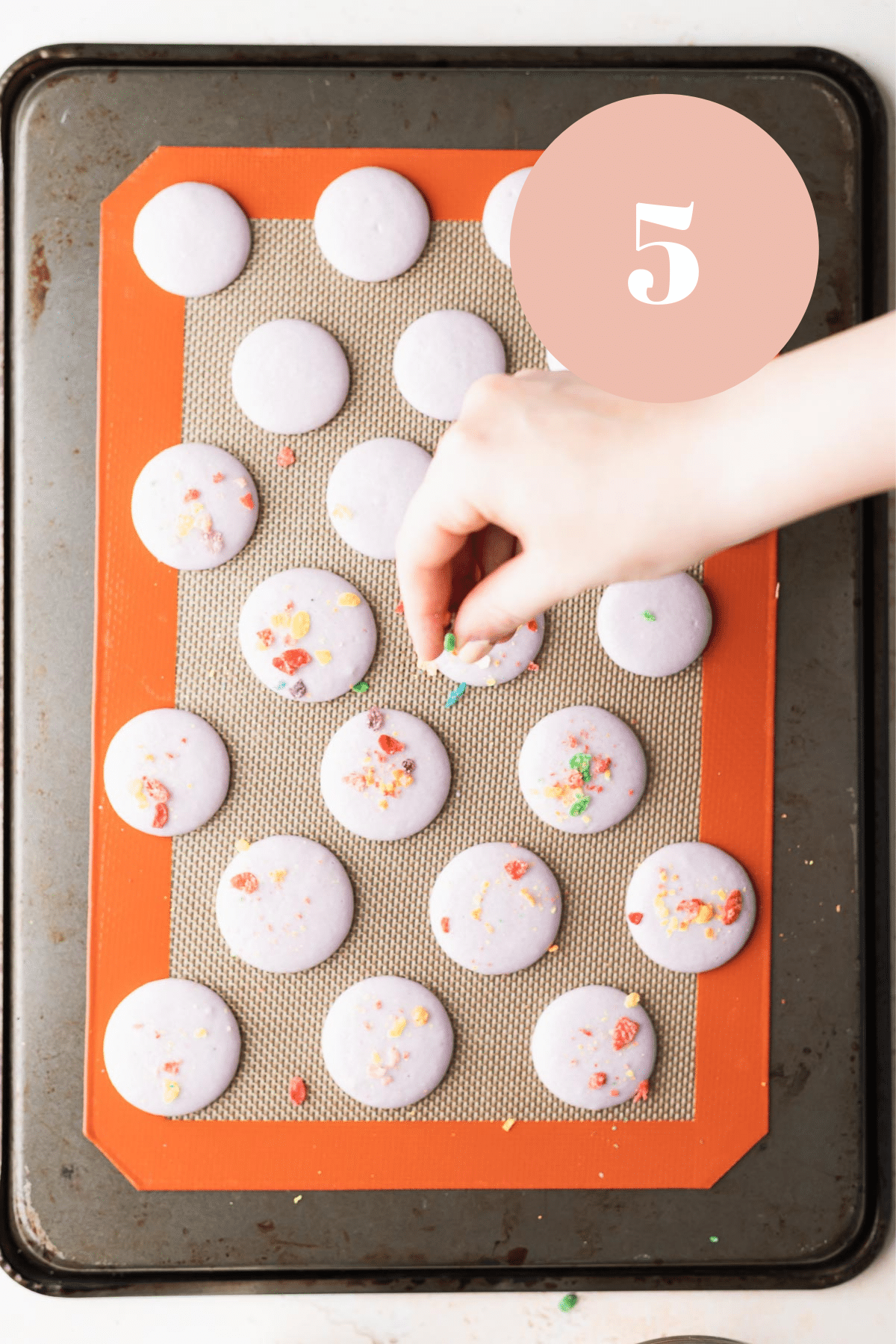 overhead shot of someone sprinkling cereal on the macaron shells