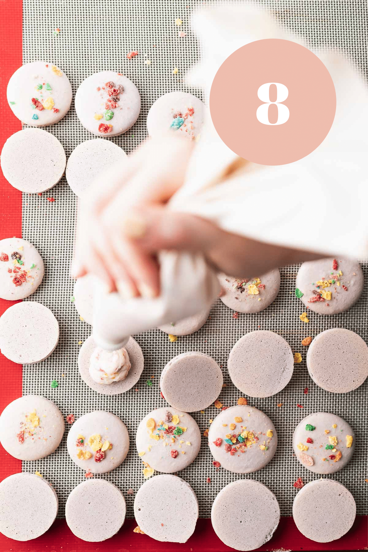 overhead shot of someone filling the macaron shells with the buttercream