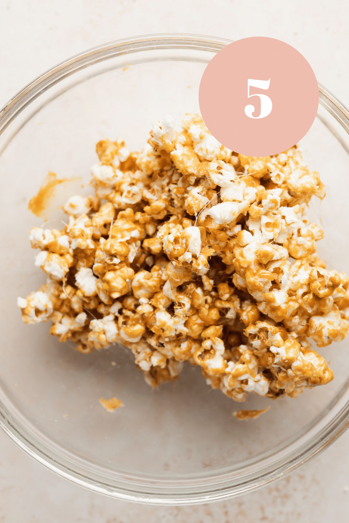 a glass bowl with the finished coated popcorn cooling