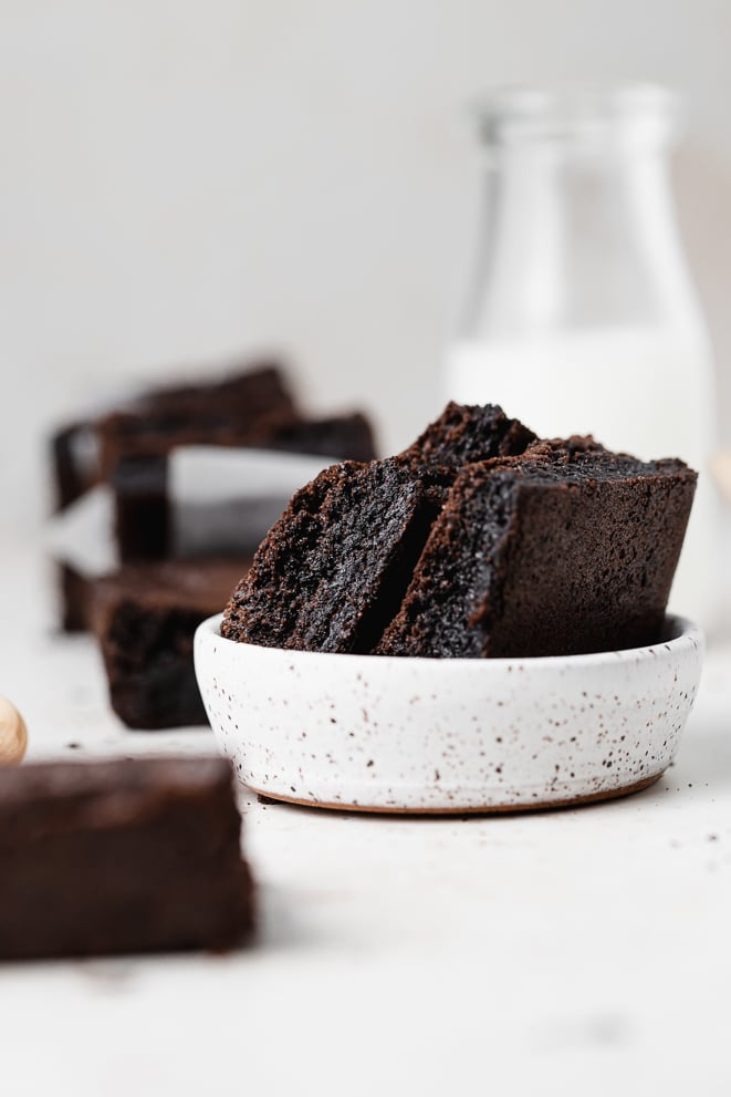 two brownies in a white ceramic dish with a jug of milk behind it
