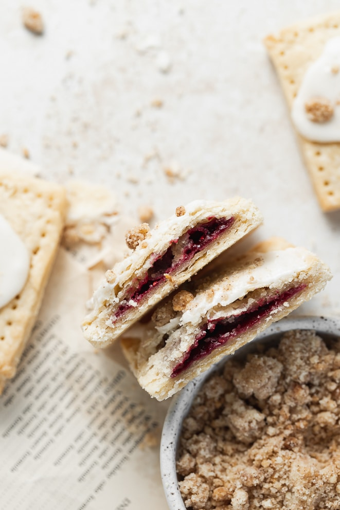 pop tart cut in half to show the jam filling next to the bowl of cinnamon crumb