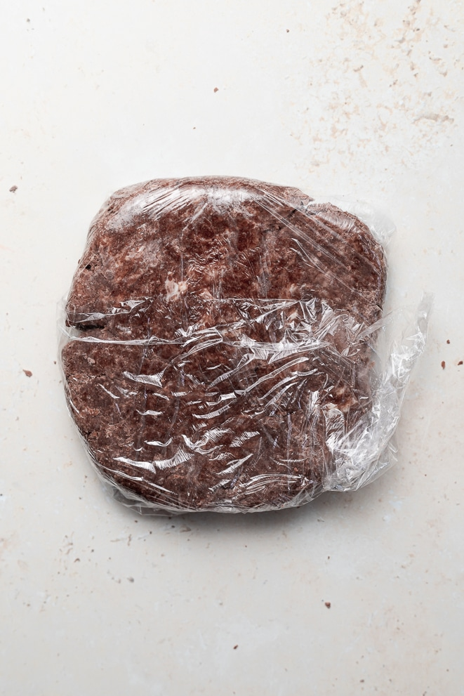 a large disk of chocolate pie dough flattened and wrapped in plastic wrap