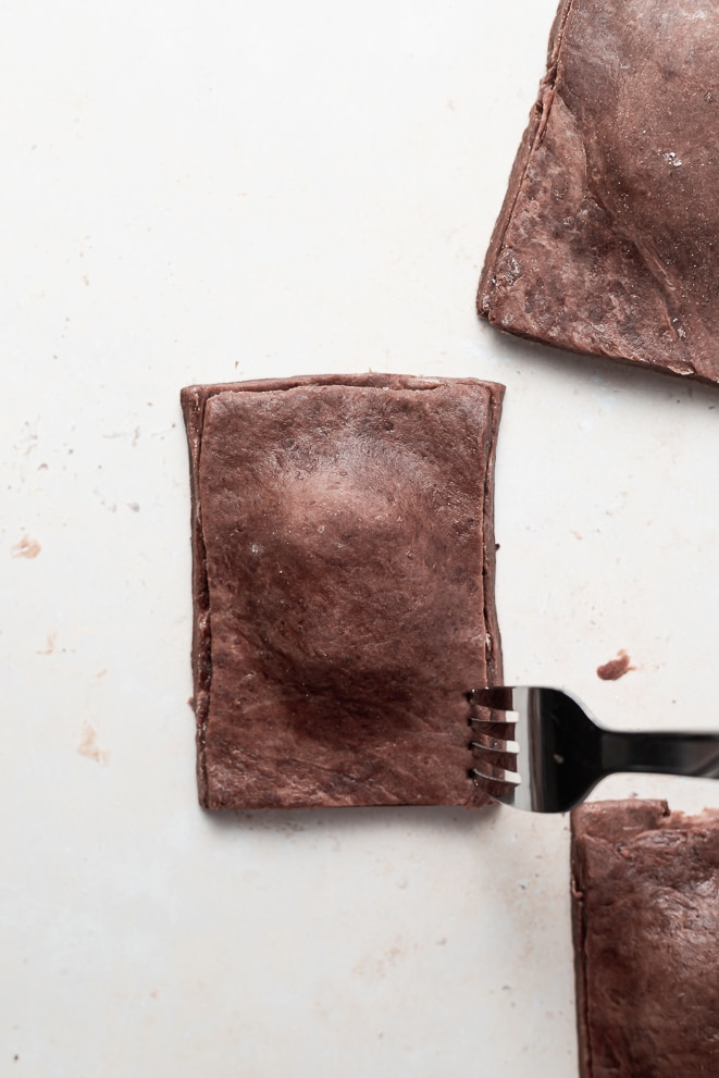 assembled pop tarts being sealed with a fork around the edges