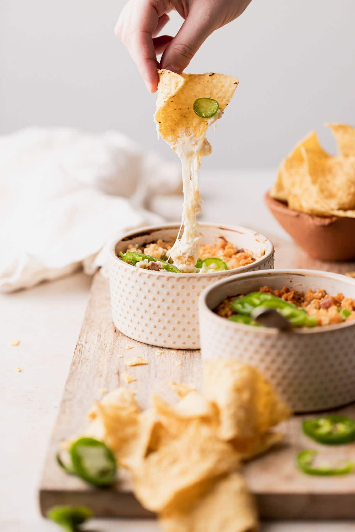 a chip pulling the dip out of the ramekin