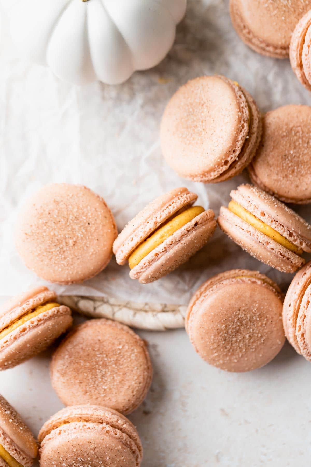 a few macarons on a cream wooden mat with a white pumpkin behind them